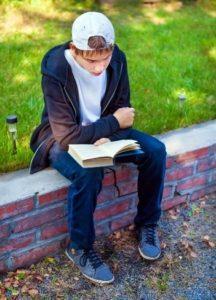 Boy reading on curb