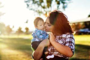 Teen mom kissing her child