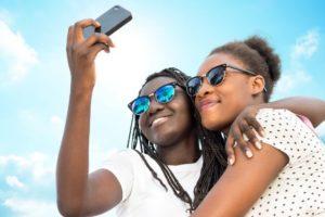 teens in sun taking selfie